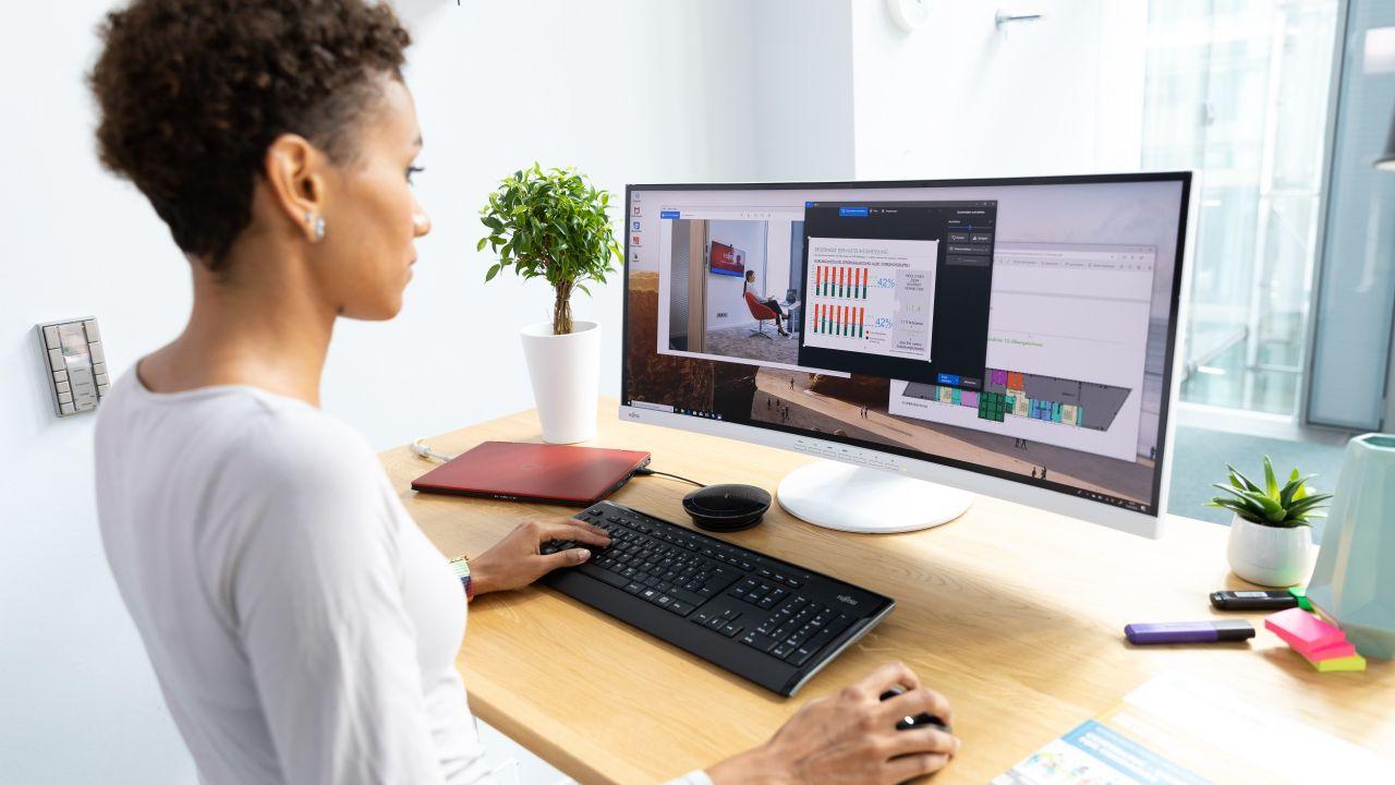 kobieta stojąca przed komputerem